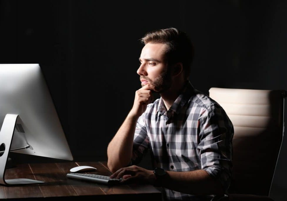 Concentrated Young Man Working In Office Alone At Night