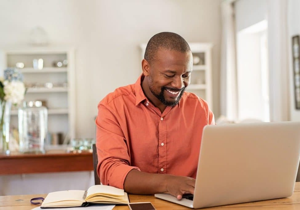 Smiling black man using laptop at home in living room. Happy mat