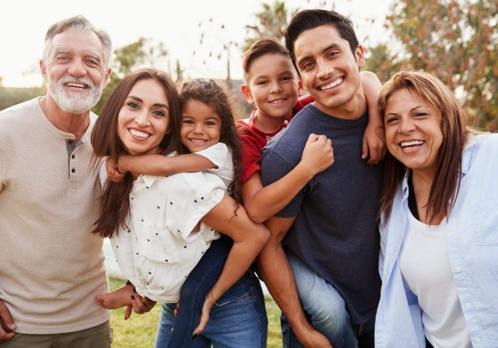 Three generation Hispanic family standing in the park, smiling t